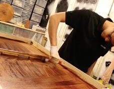 mise en peinture d'un jouet en bois par un artisan fabricant de jeu